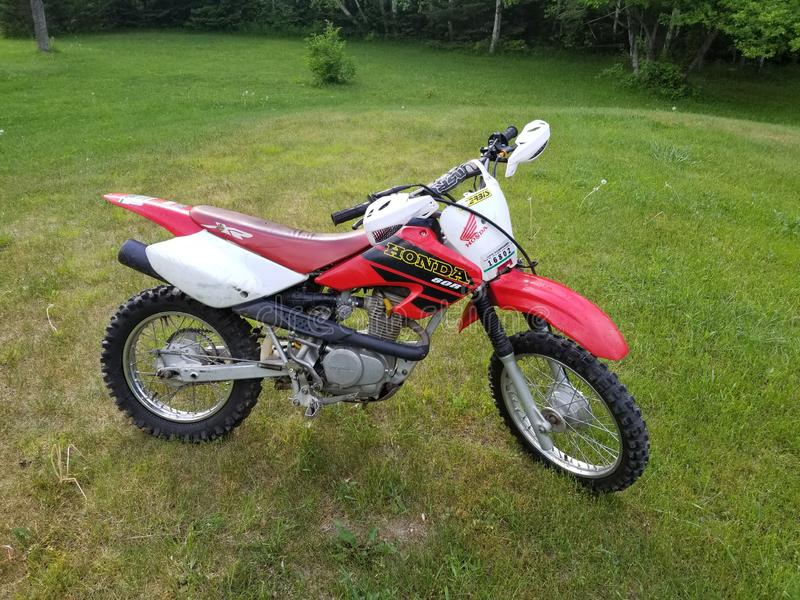 Honda dirt bike on a grassy hill during the summer royalty free stock photo