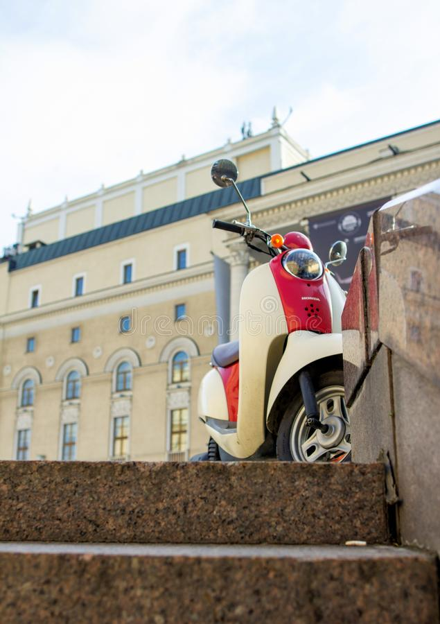 Honda`s vintage scooter on background the building of new scene of Bolshoi theatre. Moscow cityscape with transport. 2018.05.01, Moscow, Russia. Honda`s vintage stock photo