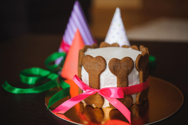 Hondcake met beenkoekjes en verjaardagshoed die wordt verfraaid stock fotografie