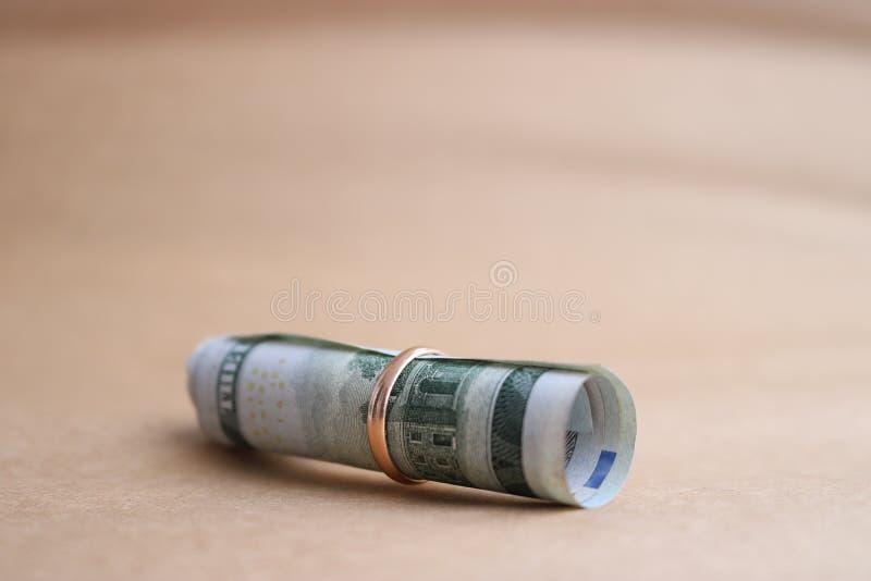 Honderd die dollarrekening in een buis binnen een trouwring wordt gerold stock foto's