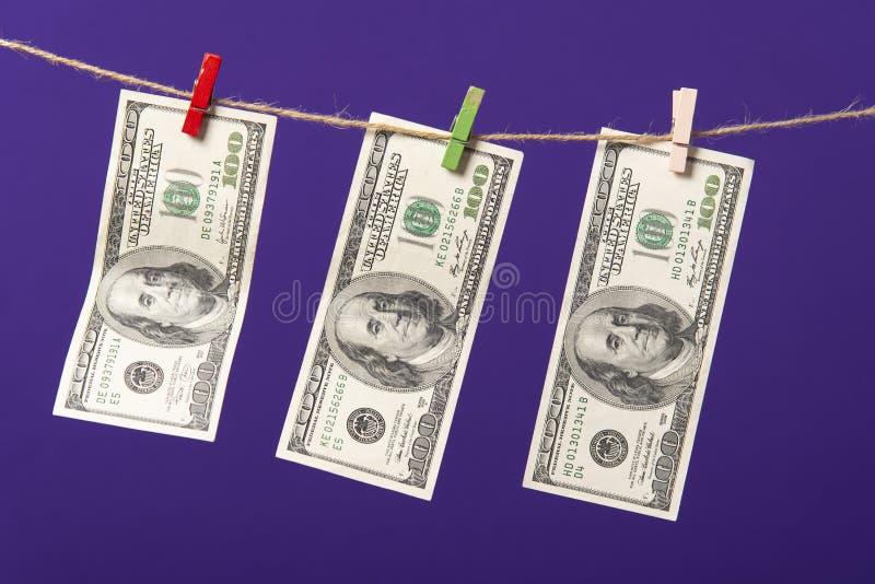 Honderd dollars die op drooglijn met houten klemmen op blauwe achtergrond hangen royalty-vrije stock foto's