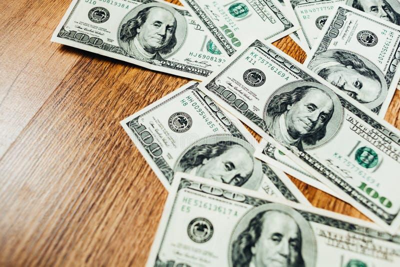 Honderd dollarsrekeningen op een houten achtergrond stock foto's