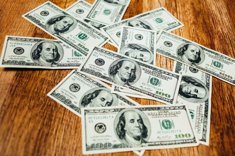 Honderd dollarsrekeningen op een houten achtergrond stock afbeelding