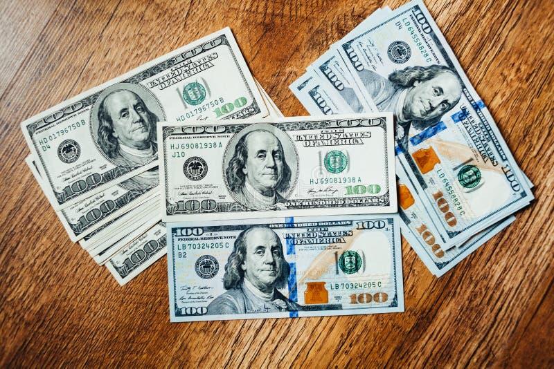 Honderd dollarsrekeningen op een houten achtergrond royalty-vrije stock foto