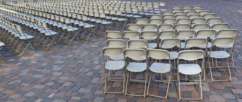 Honderden het vouwen van stoelen zijn geïnstalleerd op het granietvierkant stock foto
