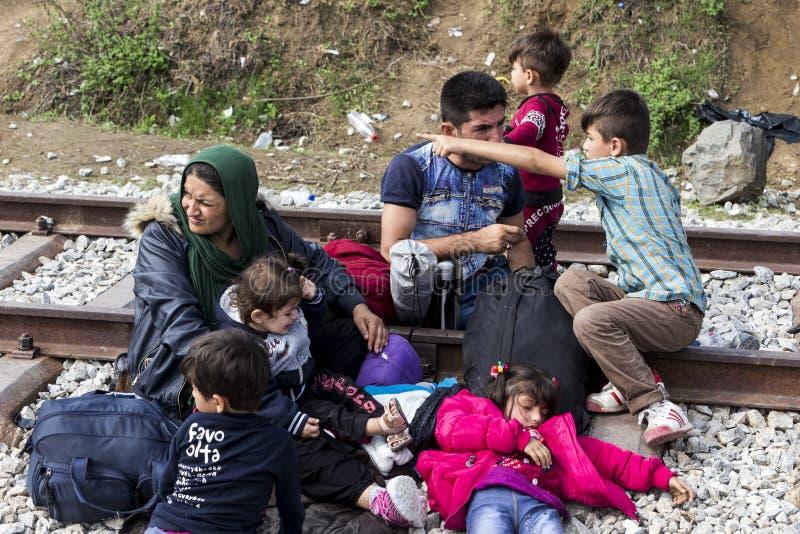 Honderden immigranten zijn in een wachttijd bij de grens tussen Greec stock afbeelding
