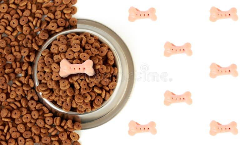 Hondkom met huisdierenvoer op de halve witte achtergrond en het verspreide droge voedsel stock afbeeldingen
