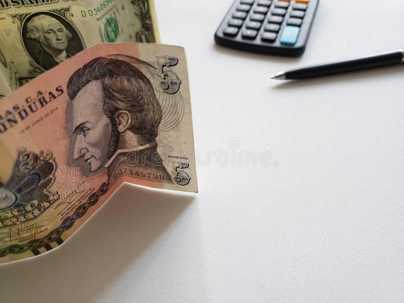 Honduran bankbiljet van vijf lempiras, Amerikaanse dollarrekening, calculator en zwarte pen royalty-vrije stock foto