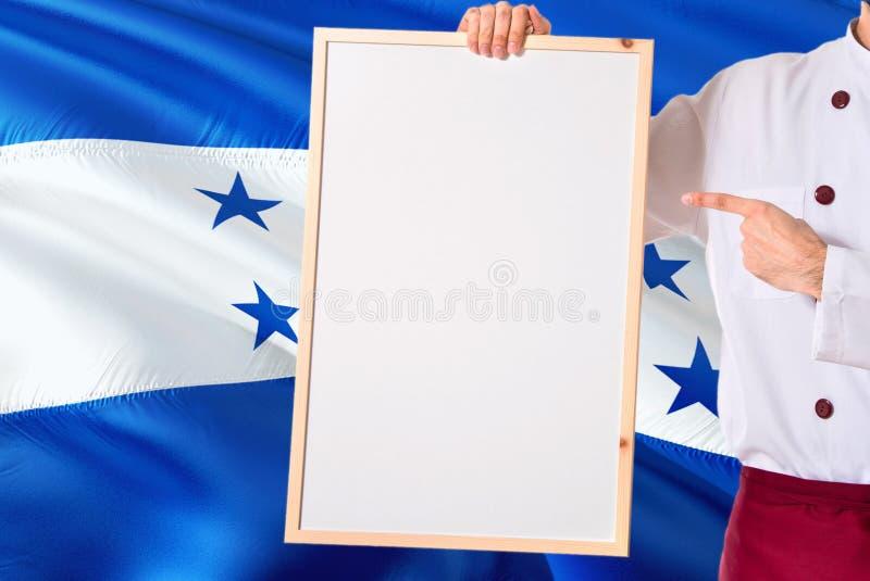 Honduranischer Chef, der leeres whiteboard Menü auf Honduras-Flaggenhintergrund hält Kochen Sie die tragende Uniform, die Raum fü lizenzfreie stockfotos