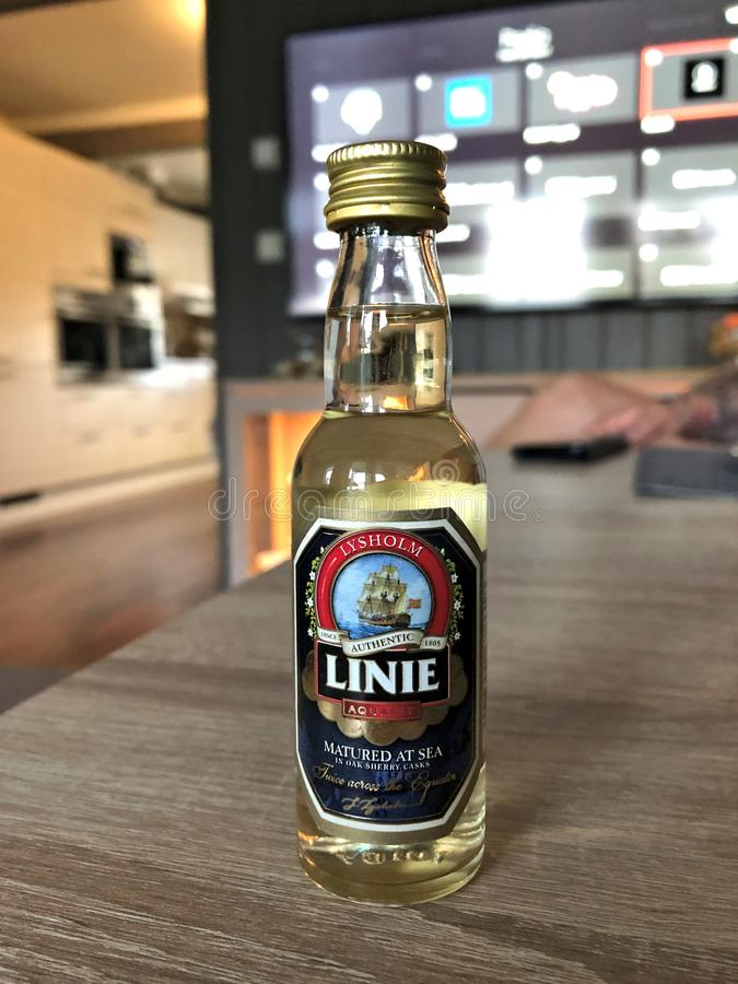 HONEFOSS, NORWAY - 7 JUN 2019: Bottle of Linie aquivit on a wooden table. Linie has been distilling the traditional Norwegian spirits from potatoes since 1805 royalty free stock image