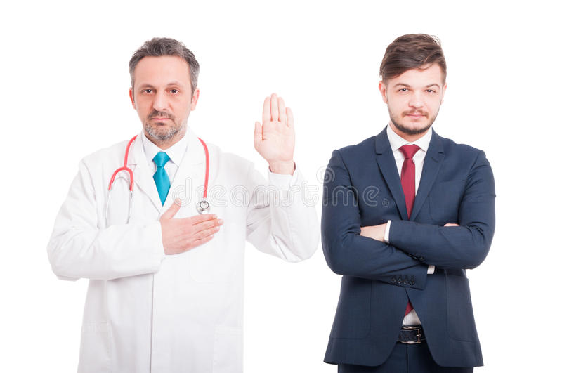Honest male medic making a vow. As devotion or loyalty concept near businessman isolated on white background stock photos