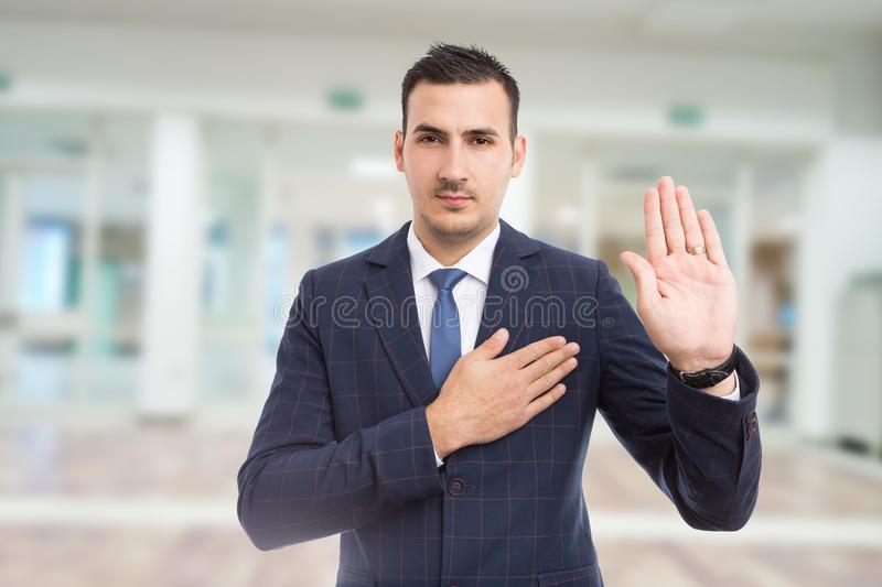 Honest trustworthy real estate agent making oath swear vow gesture. Honest trustworthy real estate agent making oath swear vow gesture on new apartment building royalty free stock image