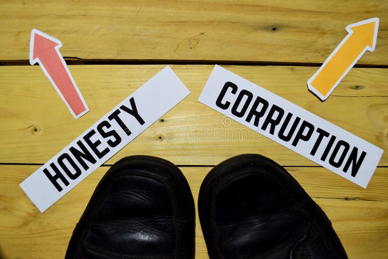 Honesty or Corruption opposite direction signs with sneakers on wooden. Vintage background. Business, education and finance concepts royalty free stock photos