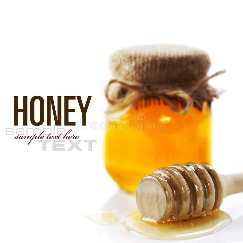 Honey. Full honey pot and honey stick over white (with sample text stock photos