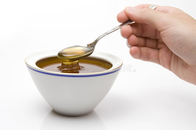 Honey. Spoon honey, white pottery dish, copy space royalty free stock image