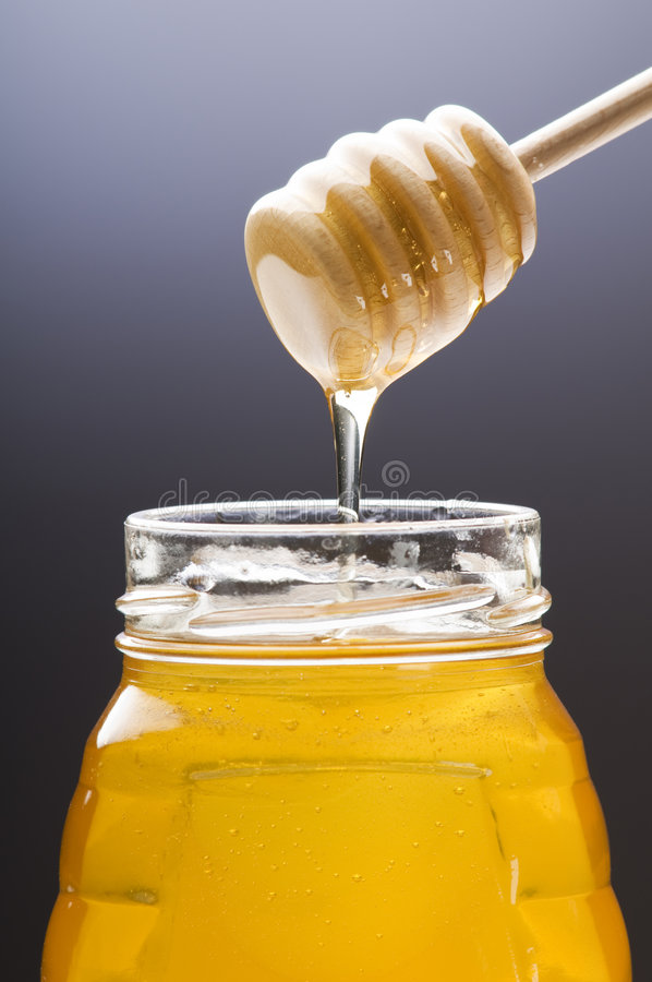 Honey. Wooden drizzler with honey pouring in the jar stock photography