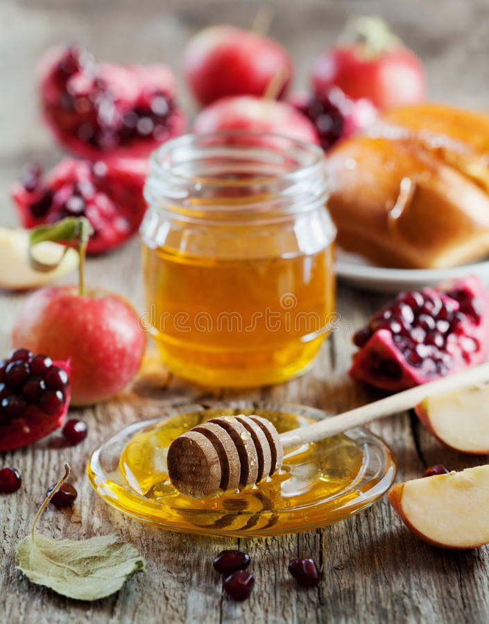 Honey, apple, pomegranate and bread hala, table set with traditional food for Jewish New Year Holiday, Rosh Hashana stock photography