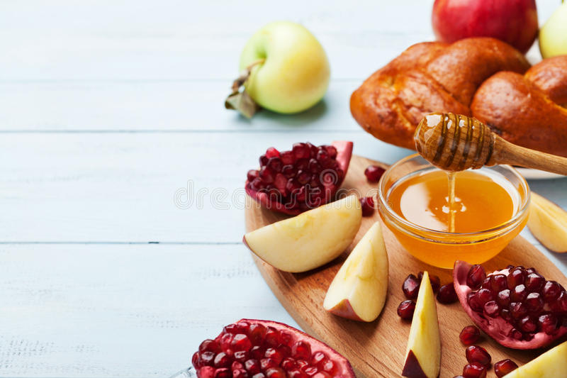 Honey, apple slices, pomegranate and hala. Table set with traditional food for Jewish New Year Holiday, Rosh Hashana. Honey, apple slices, pomegranate and hala stock image