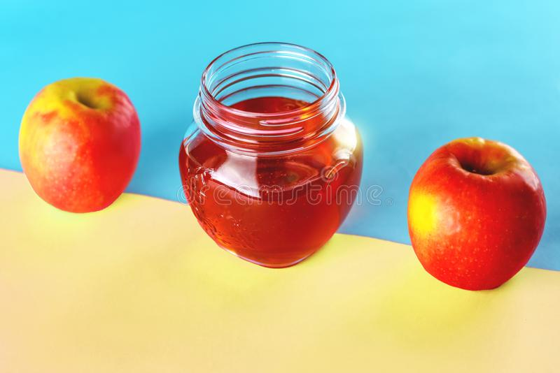 Honey and apples over blue pink background. royalty free stock image