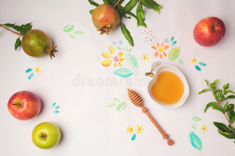 Honey, apples and pomegranate on paper background with watercolor flowers. Jewish holiday Rosh Hashanah celebration concept. stock photography