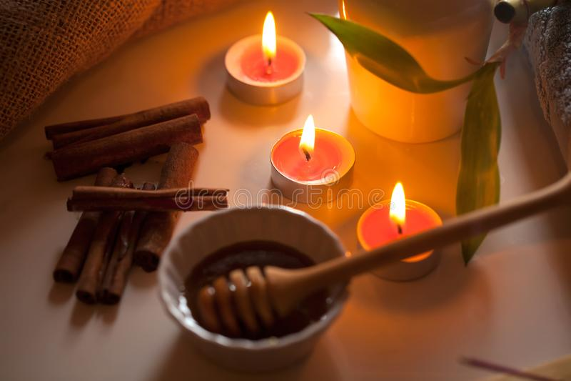 Honey and aromatic candles on table. Spa and welness concept royalty free stock photos