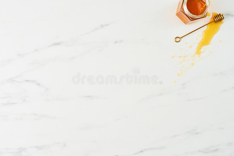 Honey background concep. Honey concept. Top view of golden dipper with honey and jar on white marble background. Horizontal flat lay with copy space royalty free stock photos
