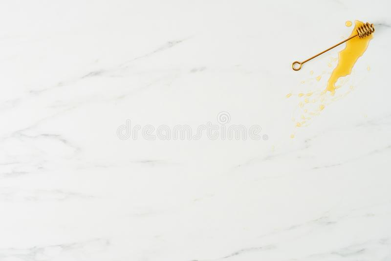 Honey background concep. Honey concept. Top view of golden dipper with honey on white marble background. Horizontal flat lay with copy space royalty free stock images