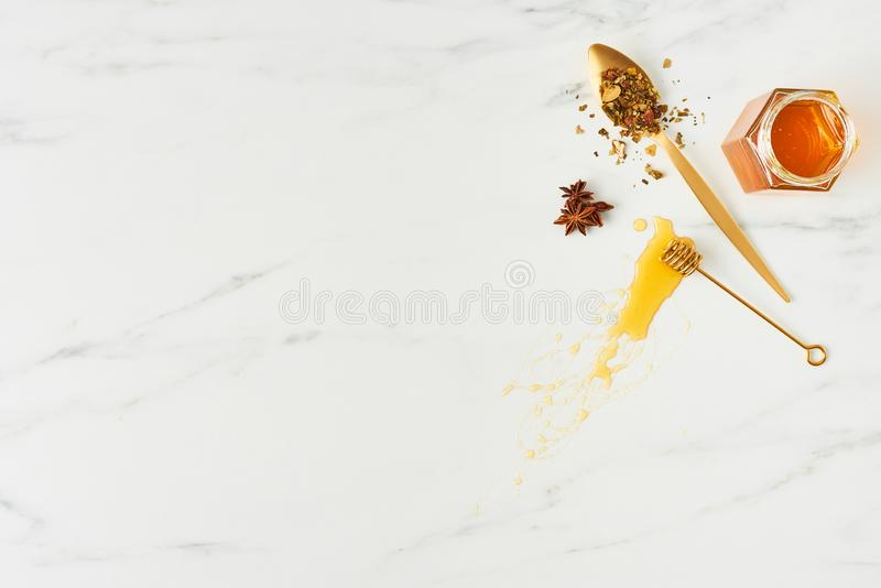 Honey background concep. Honey concept. Top view of golden dipper with honey, jar and spoon with herbs on white marble background. Horizontal flat lay with copy royalty free stock images