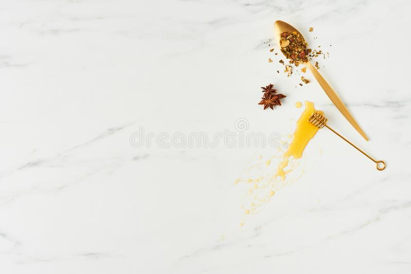 Honey background concep. Honey concept. Top view of golden dipper with honey, and spoon with herbs on white marble background. Horizontal flat lay with copy stock photography