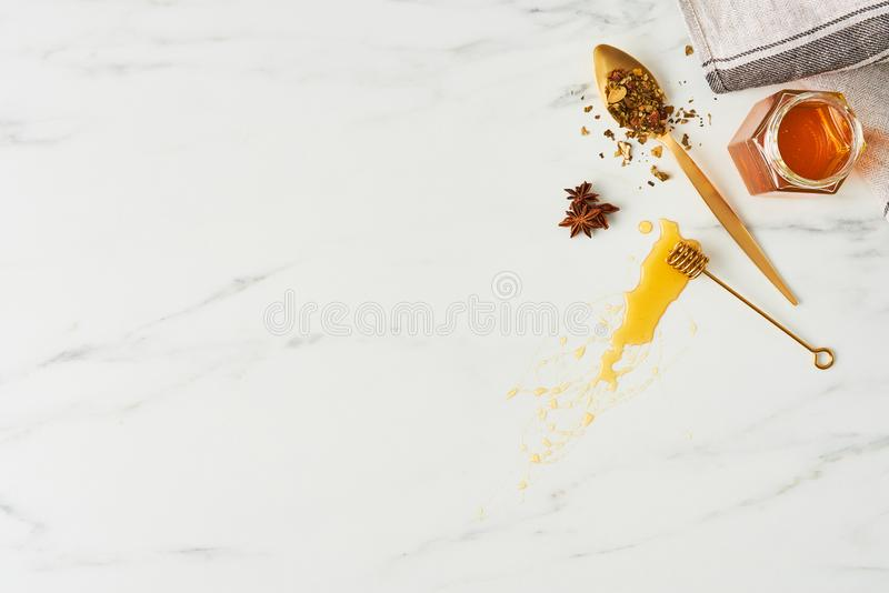Honey background concep. Honey concept. Top view of honey, golden spoon with herbs and dipper with honey on white marble background. Flat lay with copy space stock image