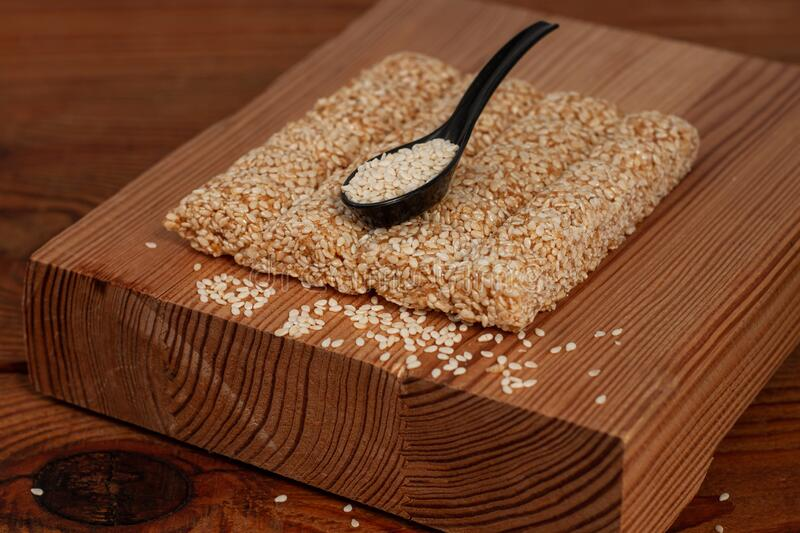 Honey bars with sesame seeds close-up on wooden background. Gozinaki sweets. Traditional oriental confection, copy space stock images