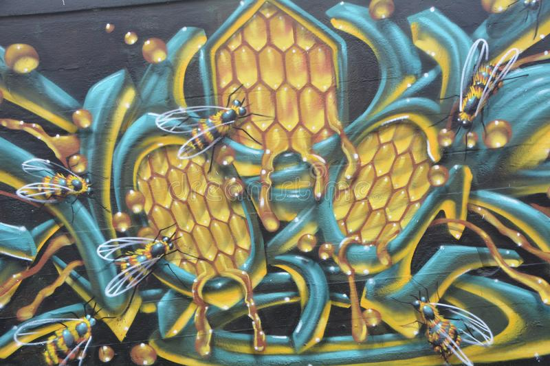 Honey bee graffiti in SE Portland, Oregon. This is honey bee graffiti decorating a building wall in SE Portland, Oregon`s industrial area stock images