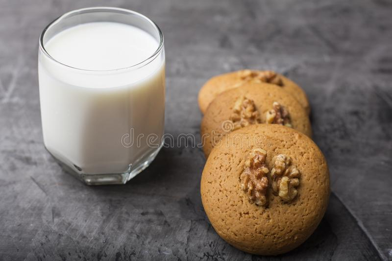 Honey biscuits with a core of walnuts on a white plate. Biscuits with powdered sugar. Dark background royalty free stock photography