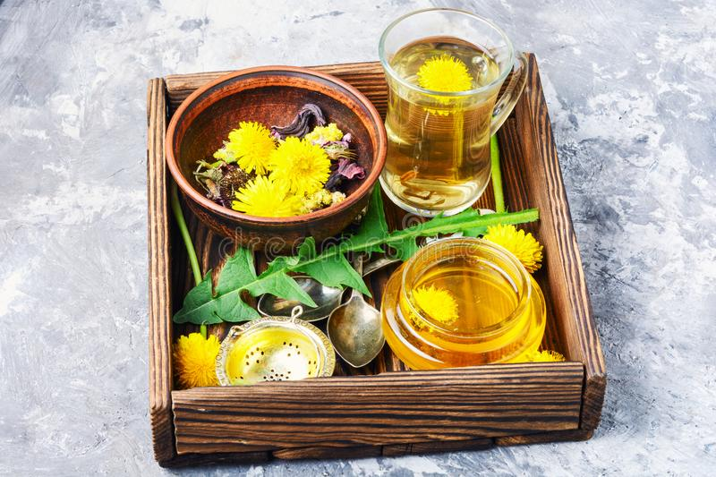 Honey from dandelion and tea. Honey from a blooming spring dandelion and cup of tea stock images