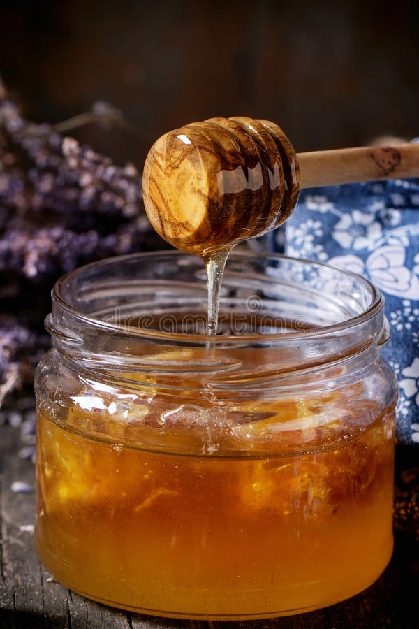 Honey, blueberries and lavender. Close up of open glass jar of liquid honey with honeycomb inside, flowing honey from honey dipper, fresh blueberries and bunch stock photo