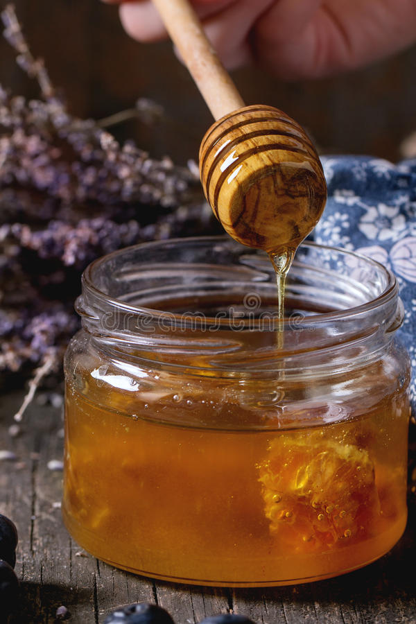 Honey, blueberries and lavender. Close up of open glass jar of liquid honey with honeycomb inside, flowing honey from honey dipper, fresh blueberries and bunch stock photos