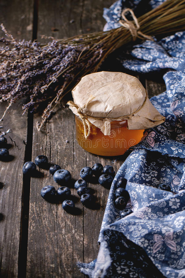 Honey, blueberries and lavender. Glass jar of liquid honey with honeycomb inside, fresh blueberries and bunch of dry lavender over old wooden table with blue royalty free stock images
