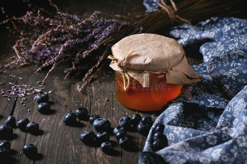 Honey, blueberries and lavender. Glass jar of liquid honey with honeycomb inside, fresh blueberries and bunch of dry lavender over old wooden table with blue stock image