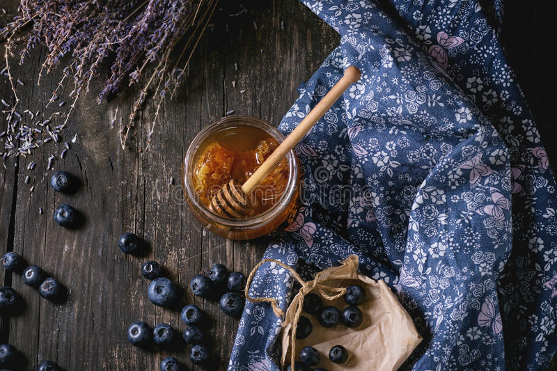 Honey, blueberries and lavender. Open glass jar of liquid honey with honeycomb and honey dipper inside, fresh blueberries and bunch of dry lavender over old stock photo