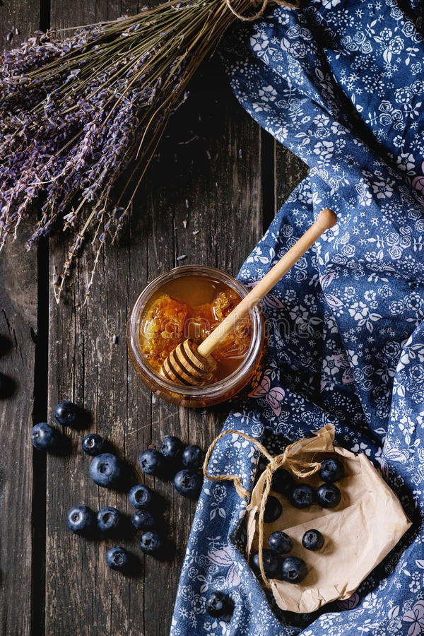 Honey, blueberries and lavender. Open glass jar of liquid honey with honeycomb and honey dipper inside, fresh blueberries and bunch of dry lavender over old stock image