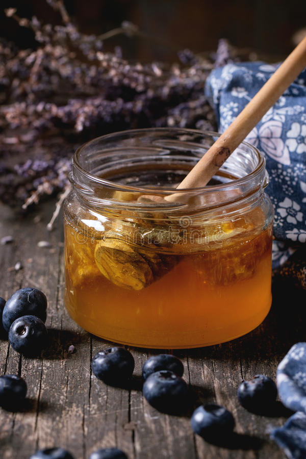 Honey, blueberries and lavender. Open glass jar of liquid honey with honeycomb and honey dipper inside, fresh blueberries and bunch of dry lavender over old royalty free stock photo