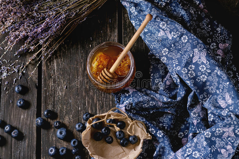 Honey, blueberries and lavender. Open glass jar of liquid honey with honeycomb and honey dipper inside, fresh blueberries and bunch of dry lavender over old stock images