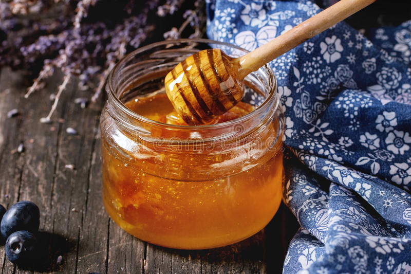 Honey, blueberries and lavender. Open glass jar of liquid honey with honeycomb inside, flowing honey from honey dipper, fresh blueberries and bunch of dry stock photo