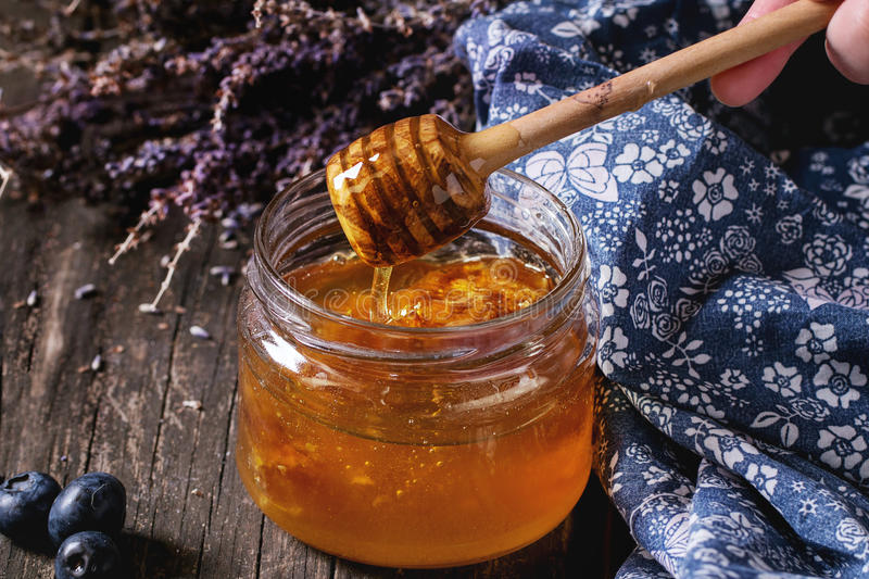 Honey, blueberries and lavender. Open glass jar of liquid honey with honeycomb inside, flowing honey from honey dipper, fresh blueberries and bunch of dry stock images