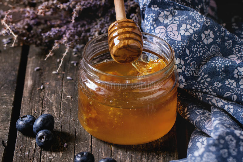 Honey, blueberries and lavender. Open glass jar of liquid honey with honeycomb inside, flowing honey from honey dipper, fresh blueberries and bunch of dry royalty free stock images