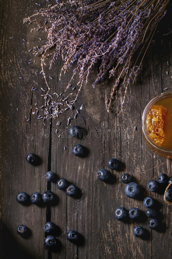 Honey, blueberries and lavender. Open glass jar of liquid honey with honeycomb inside, fresh blueberries and bunch of dry lavender over old wooden table with royalty free stock image