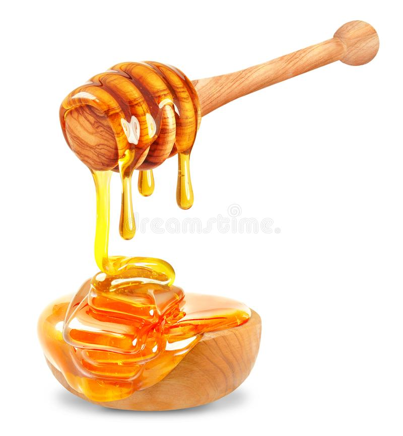 Honey and bowl. Honey dripping into a wooden bowl on a white background stock photography