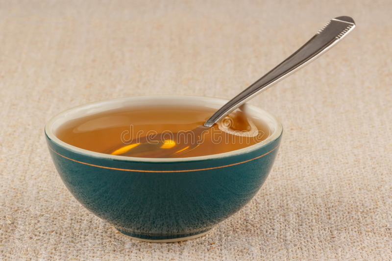 Honey in bowl. Honey in green porcelain bowl, with metal teaspoon, on rustic table cloth royalty free stock images
