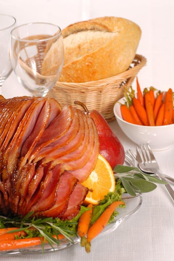 Honey and brown sugar glazed Easter ham. Brown sugar and honey glazed Easter ham with fruit and carrots