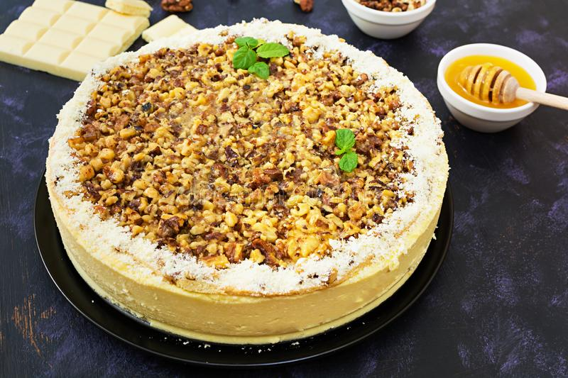Honey cake with cottage cheese, oranges and nuts, decorated with white chocolate royalty free stock image